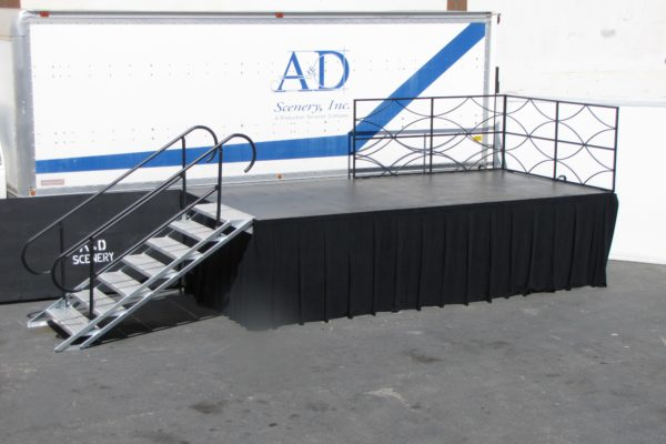 Staging with safety railings, skirting, & steel deck step unit