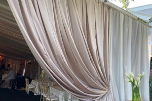 Outdoor-wedding-decor-tent-champagne-satin-perimeter-ivory-sheer-layering-drapery-event-rental