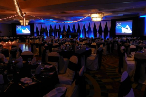 Quest-Events-Corporate-Event-Meeting-Drape-Hourglass-Stage-Backdrop-AV-Surround-White-Black-Uplighting