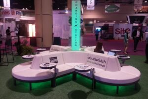 tradeshow-furnishing-rental-event-quest-brandedp-seating-configuration-clover-totally-mod-swing-tables-underlighting-min-min